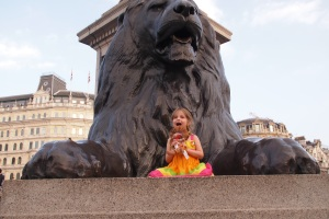 Lily on top of one of the Trafalgar Square lions after seeing The Lion King musical performance. She's even holding her toy Simba.